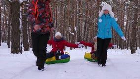 Οικογένεια με τα παιδιά που χαλαρώνουν στις διακοπές Χριστουγέννων οδηγώντας το χιόνι sauser και γελώντας Μπαμπάς mom και γύρος κ απόθεμα βίντεο