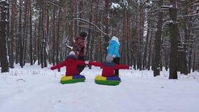 Οικογένεια με τα παιδιά που χαλαρώνουν στις διακοπές Χριστουγέννων οδηγώντας το χιόνι sauser και γελώντας Μπαμπάς mom και γύρος κ φιλμ μικρού μήκους