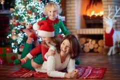 Οικογένεια με τα παιδιά στο χριστουγεννιάτικο δέντρο και την εστία στοκ φωτογραφία με δικαίωμα ελεύθερης χρήσης