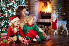 Οικογένεια με τα παιδιά στο χριστουγεννιάτικο δέντρο και την εστία στοκ εικόνες με δικαίωμα ελεύθερης χρήσης