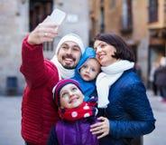 Οικογένεια με τα παιδιά που περπατούν την πόλη και που κάνουν selfie Στοκ Εικόνες