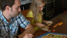 Οικογένεια με τη μικρή κόρη τους που παίζει το επιτραπέζιο παιχνίδι Στοκ Εικόνες