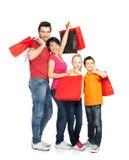 Οικογένεια με τις τσάντες αγορών που στέκονται στο στούντιο Στοκ Εικόνες