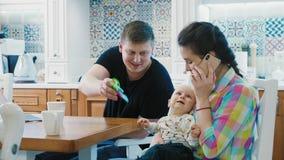 Οικογένεια με τις ψηφιακές συσκευές χρήσης αγοράκι στον πίνακα προγευ φιλμ μικρού μήκους