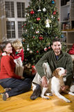 Οικογένεια με το αγόρι και το σκυλί από το χριστουγεννιάτικο δέντρο Στοκ φωτογραφία με δικαίωμα ελεύθερης χρήσης