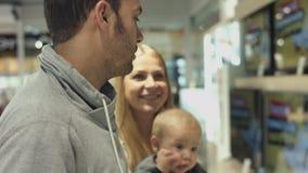 Οικογένεια με το γιο μωρών που επιλέγει τις οικιακές συσκευές στο κατάστημα απόθεμα βίντεο
