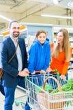 Οικογένεια με το κάρρο αγορών στο μανάβικο στοκ εικόνες με δικαίωμα ελεύθερης χρήσης