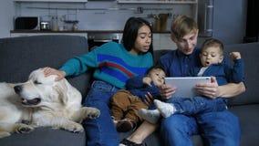 Οικογένεια με το σκυλί κατοικίδιων ζώων που κοιτάζει βιαστικά on-line στο PC ταμπλετών φιλμ μικρού μήκους