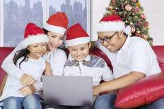 Οικογένεια με το lap-top χρήσης καπέλων Santa στον καναπέ Στοκ εικόνα με δικαίωμα ελεύθερης χρήσης