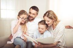 Οικογένεια με δύο παιδιά που κάθονται στον καναπέ και που διαβάζουν το βιβλίο από κοινού στοκ εικόνα με δικαίωμα ελεύθερης χρήσης