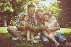 Οικογένεια με δύο παιδιά στο βιβλίο ανάγνωσης λιβαδιών από κοινού στοκ φωτογραφία