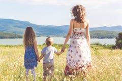 Οικογένεια: μητέρα, κόρη και γιος στο chamomile τομέα Στοκ εικόνες με δικαίωμα ελεύθερης χρήσης