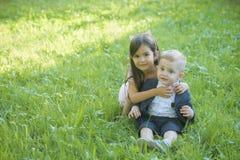 Οικογένεια, παιδιά, αδελφός και αδελφή στην πράσινη χλόη Στοκ Εικόνες