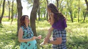 Οικογένεια Πατέρας, έγκυες μητέρα και κόρη υπαίθρια Περίπατος στο πάρκο πόλεων φιλμ μικρού μήκους
