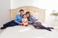Οικογένεια, πατρότητα και έννοια παιδιών - ευτυχές παιχνίδι μητέρων, πατέρων και γιων μαζί με τη teddy αρκούδα στο κρεβάτι μέσα στοκ φωτογραφίες