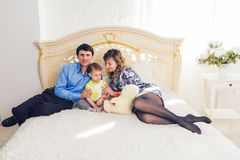 Οικογένεια, πατρότητα και έννοια παιδιών - ευτυχές παιχνίδι μητέρων, πατέρων και γιων μαζί με τη teddy αρκούδα στο κρεβάτι μέσα στοκ φωτογραφίες με δικαίωμα ελεύθερης χρήσης