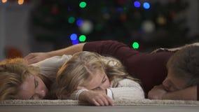Οικογένεια πεσμένος κοιμισμένος κάτω από το χριστουγεννιάτικο δέντρο που περιμένει Άγιο Βασίλη, πεποίθηση σε μαγικό απόθεμα βίντεο