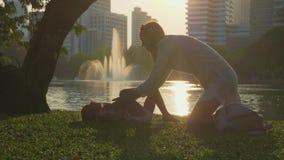 Οικογένεια που έχει τη διασκέδαση στο πάρκο με τη λίμνη και τους ουρανοξύστες στο υπόβαθρο απόθεμα βίντεο