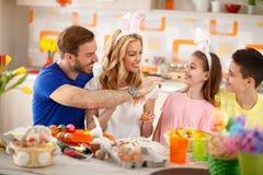 Οικογένεια που έχει τη διασκέδαση χρωματίζοντας τα αυγά Πάσχας στοκ εικόνες
