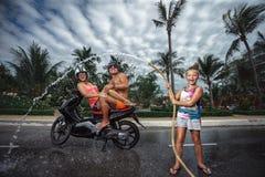Οικογένεια που έχει τη διασκέδαση με την καταβρέχοντας θερινή βροχή μανικών κήπων Στοκ Φωτογραφία