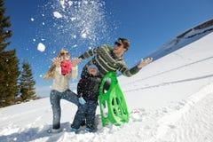 Οικογένεια που έχει τη διασκέδαση στο φρέσκο χιόνι στο χειμώνα Στοκ Εικόνες