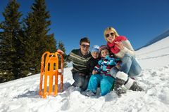 Οικογένεια που έχει τη διασκέδαση στο φρέσκο χιόνι στο χειμώνα Στοκ Φωτογραφίες