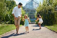 Οικογένεια που έχει τη διασκέδαση υπαίθρια Ευτυχείς νέοι γονείς, παιχνίδι παιδιών Στοκ φωτογραφία με δικαίωμα ελεύθερης χρήσης