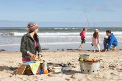 Οικογένεια που έχει τη σχάρα στη χειμερινή παραλία Στοκ Εικόνες
