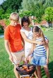 Οικογένεια που έχει τη σχάρα Στοκ φωτογραφία με δικαίωμα ελεύθερης χρήσης