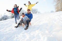 Οικογένεια που έχει τη διασκέδαση Sledging κάτω από το χιονώδες Hill Στοκ Εικόνες