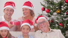 Οικογένεια που ανταλλάσσει τα χριστουγεννιάτικα δώρα απόθεμα βίντεο