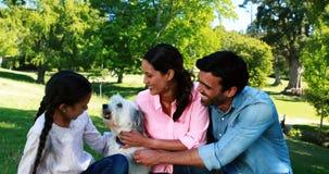 Οικογένεια που απολαμβάνει μαζί με το σκυλί κατοικίδιων ζώων τους στο πάρκο απόθεμα βίντεο