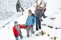 Οικογένεια που απολαμβάνει τον περίπατο μέσω του χιονώδους τοπίου στοκ φωτογραφία με δικαίωμα ελεύθερης χρήσης