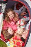 Οικογένεια που απολαμβάνει τις διακοπές στρατοπέδευσης στη θέση για κατασκήνωση στοκ εικόνες
