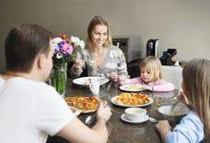 Οικογένεια που γελά γύρω από ένα καλό γεύμα στην κουζίνα Στοκ φωτογραφία με δικαίωμα ελεύθερης χρήσης