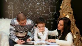 Οικογένεια που διαβάζει ένα βιβλίο με ένα παραμύθι Χριστουγέννων απόθεμα βίντεο