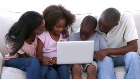Οικογένεια που εξετάζει το lap-top στον καναπέ απόθεμα βίντεο