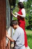 Οικογένεια που επισκευάζει το σπίτι στο εξωτερικό από κοινού. Στοκ Εικόνες