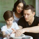 Οικογένεια που εργάζεται στη ρόδα αγγειοπλαστών Στοκ Εικόνες