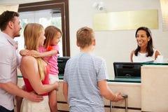 Οικογένεια που ελέγχει μέσα στην υποδοχή ξενοδοχείων Στοκ Φωτογραφία