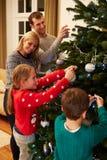 Οικογένεια που διακοσμεί το χριστουγεννιάτικο δέντρο στο σπίτι από κοινού Στοκ Εικόνες