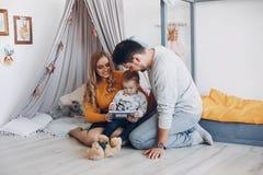 Οικογένεια που κάθεται στο σπίτι στο πάτωμα στοκ φωτογραφίες
