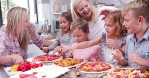 Οικογένεια που κατασκευάζει την πίτσα στην κουζίνα από κοινού απόθεμα βίντεο