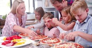 Οικογένεια που κατασκευάζει την πίτσα στην κουζίνα από κοινού φιλμ μικρού μήκους