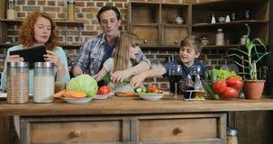Οικογένεια που μαγειρεύει μαζί να χρησιμοποιήσει τη συνταγή από τους γονείς υπολογιστών ταμπλετών με δύο παιδιά στην κουζίνα που  φιλμ μικρού μήκους