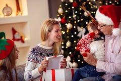 Οικογένεια που μοιράζεται το δώρο στη χαμογελώντας μητέρα Χριστουγέννων που δίνει το παρόν Στοκ Φωτογραφίες
