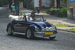 Οικογένεια που οδηγεί τον κάνθαρο του Volkswagen στη retrocar φυλή Στοκ Φωτογραφία