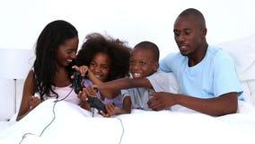Οικογένεια που παίζει τα τηλεοπτικά παιχνίδια στο κρεβάτι απόθεμα βίντεο