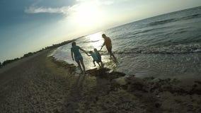 Οικογένεια που περπατά κατά μήκος της θάλασσας στο ηλιοβασίλεμα φιλμ μικρού μήκους