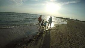 Οικογένεια που περπατά κατά μήκος της θάλασσας στο ηλιοβασίλεμα απόθεμα βίντεο